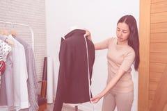 Il sarto dello stilista sta misurando il rivestimento del vestito dell'ufficio fotografia stock libera da diritti