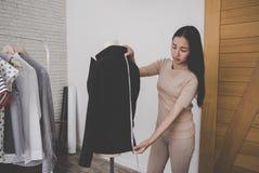 Il sarto dello stilista sta misurando il rivestimento del vestito dell'ufficio immagine stock libera da diritti