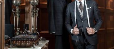 Il sarto passa i vestiti diversi d'adattamento costosi Immagine Stock Libera da Diritti
