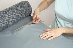 Il sarto taglia con il bullone di forbici del panno blu scuro Fotografie Stock