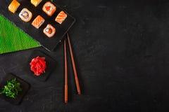Il sashimi dei sushi ed i rotoli di sushi stabiliti sono servito sull'ardesia di pietra immagine stock libera da diritti