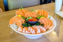 Il sashimi di color salmone ha messo sul fuoco selettivo della ciotola bianca Fotografia Stock