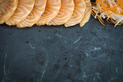 Il sashimi di color salmone su fondo di pietra nero, confine fotografia stock libera da diritti