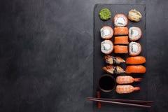 Il sashimi rassodato dei sushi con i rotoli Philadelphia del salmone, del gamberetto, dell'anguilla e di sushi è servito sull'ard Immagini Stock Libere da Diritti