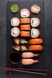 Il sashimi rassodato dei sushi con i rotoli Philadelphia del salmone, del gamberetto, dell'anguilla e di sushi è servito sull'ard Fotografia Stock Libera da Diritti