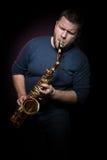 Il sassofonista felice gioca la musica sul sax fotografie stock libere da diritti