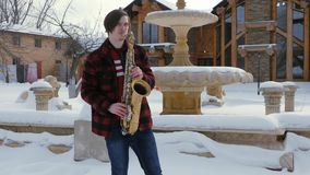 Il sassofonista gioca il sassofono, nell'inverno stock footage