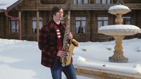 Il sassofonista gioca il sassofono, nell'inverno archivi video