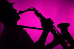 Il sassofono ha giocato nella priorità bassa di colore rosa della siluetta Immagini Stock Libere da Diritti