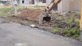Il secchio degli sterri di scavatura di un escavatore meccanico su un cantiere archivi video