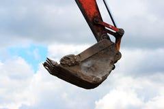 Il secchio dell'escavatore è alzato verso l'alto, in cui le pale dei lavoratori sono nascoste protezione dal furto al contro fotografia stock libera da diritti
