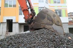 Il secchio dell'escavatore scava sulla ghiaia Fotografie Stock Libere da Diritti