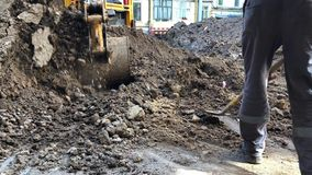 Il secchio dell'escavatore versa la terra Impianto idraulico del lavoro di riparazione archivi video