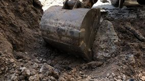 Il secchio dell'escavatore versa la terra Impianto idraulico del lavoro di riparazione video d archivio