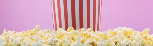 il secchio sta su un popcorn sparso, su un fondo rosa fotografia stock