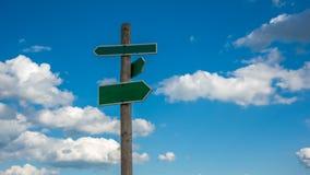 Il segnale di direzione con il fondo delle nuvole fotografia stock