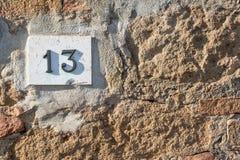 Il segnale stradale su una casa che legge il numero tredici ha fatto dalle cifre metalliche su una base di marmo immagine stock