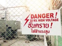 Il segno ad alta tensione del pericolo d'avvertimento e la lingua tailandese significano il pericolo h Fotografie Stock