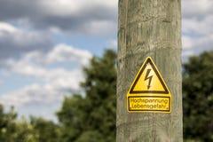 Il segno ad alta tensione tedesco ha montato sul palo di legno con gli alberi verdi nel fondo Immagini Stock Libere da Diritti
