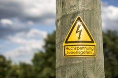 Il segno ad alta tensione tedesco ha montato sul palo di legno con gli alberi verdi nel fondo Fotografie Stock Libere da Diritti