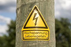 Il segno ad alta tensione tedesco ha montato sul palo di legno con gli alberi verdi nel fondo Immagine Stock