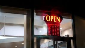 Il segno aperto del deposito di affari accende fuori dalla finestra anteriore stock footage