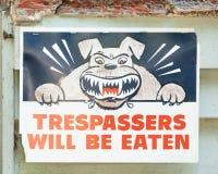 Il segno che dichiara i CONTRAVVENTORI SARÀ MANGIATO con il simbolo arrabbiato del cane Immagine Stock