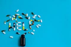 Il segno di aiuto fatto delle pillole variopinte ha straripato una bottiglia Fotografia Stock Libera da Diritti