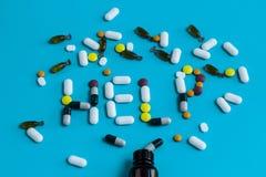 Il segno di aiuto fatto delle pillole variopinte ha straripato una bottiglia su un blu Immagine Stock