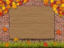 Il segno di legno sui rami dell'acero di autunno del muro di mattoni erba e l'albero caduto va Immagine Stock