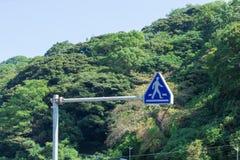 Il segno di simbolo per la gente attraverso alla via Immagine Stock