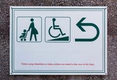 Il segno e lo storpio del passeggiatore di bambino firmano con la freccia per le direzioni fotografie stock