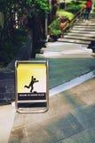 Il segno giallo di simbolo si guarda dal segno irregolare del pavimento fotografia stock