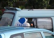 Il segno o la carrozza della luce del taxi firma nel colore blu e bianco sul colore blu del tetto dell'automobile alla via immagine stock