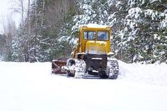 Il selezionatore del trattore a cingoli pulisce la neve su un sentiero forestale Fotografia Stock