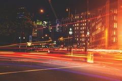 Il semaforo dell'automobile di ora di punta trascina a Londra alla notte fotografia stock libera da diritti