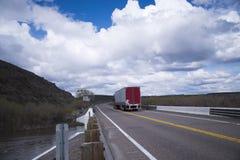 il Semi-camion ed il rimorchio guidano sul ponte della strada sopra il fiume Immagini Stock Libere da Diritti