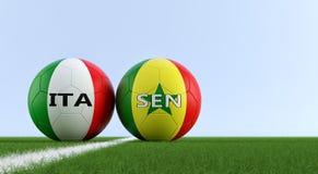 Il Senegal contro Partita di calcio dell'Italia - palloni da calcio nei colori nazionali di Senegals e di Italys su un campo di c Fotografie Stock