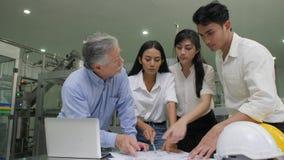 Il senior manager e gli ingegneri industriali team la verifica i piani di produzione in una fabbrica