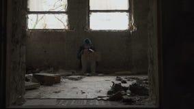 Il senzatetto affamato congelato con aiuto del piatto si siede in costruzione abbandonata video d archivio