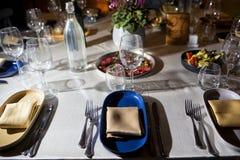 Il servizio con lo stemware di vetro e dell'argenteria per un evento fa festa Fotografia Stock Libera da Diritti