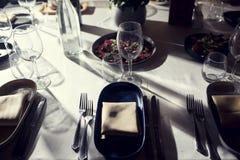 Il servizio con lo stemware di vetro e dell'argenteria per un evento fa festa Fotografia Stock