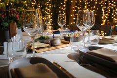 Il servizio con lo stemware di vetro e dell'argenteria per un evento fa festa Fotografie Stock