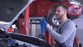 Il servizio dell'automobile, livello di olio attraente dei controlli del tipo del tecnico durante la riparazione dell'automobile  stock footage