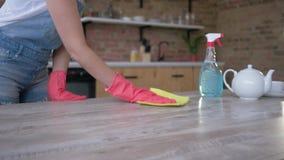 Il servizio di pulizia, donna in guanti lava la tavola con lo straccio ed il detersivo alla cucina stock footage