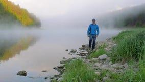 Il signore guarda l'acqua di fiume calma con la nebbia spessa di mattina archivi video