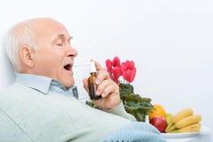 Il signore senior stancato usa il suo spruzzo della gola irritata fotografia stock libera da diritti