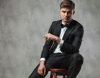 Il signore sexy ha vestito elegante la seduta ed indicare il lato Fotografia Stock Libera da Diritti