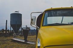 Il silo del metallo ed il camion giallo sulla vecchia azienda agricola fotografia stock libera da diritti