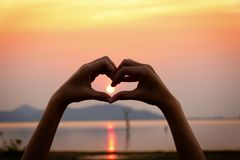 Il simbolo della mano del cuore della siluetta con il fondo di tramonto Fotografia Stock Libera da Diritti